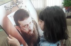 ابن الشيخ خضر عدنان يحمل صورة ابيه.jpg