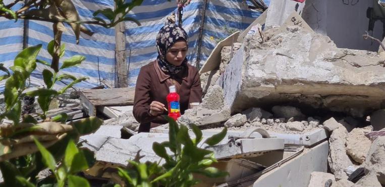 الفنانة سجى موسى ترسم على البلاط المكسور من منزل عائلتها في رفح جنوب قطاع غزة