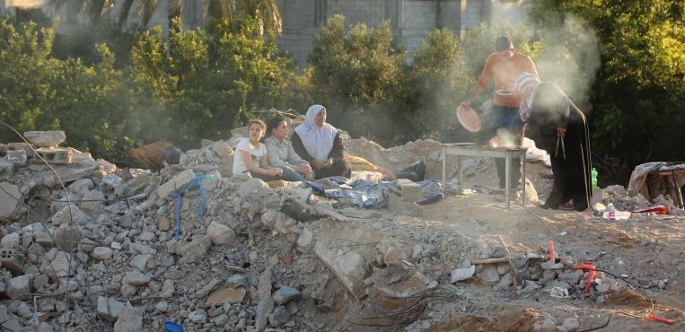 عائلة فلسطينية تتناول غداء لحوم الأضاحي فوق منزلها المدمر من قبل الطيران الاسرائيلي